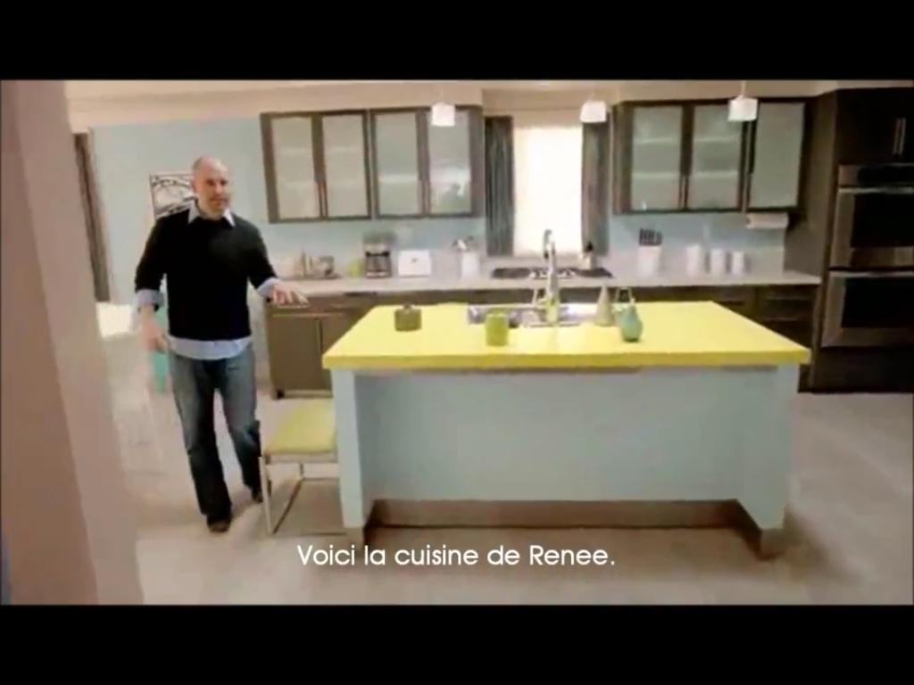 La vaste cuisine de renee tandis que lîlot se décline en bleu et jaune le reste des éléments de cuisine est noir un petit tabouret est installé contre