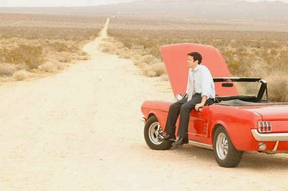 man sitting on broken down car in desert