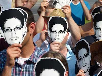 Protesters wear paper Snowden masks