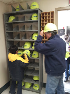 Tour participants select hard hats and safety glasses.