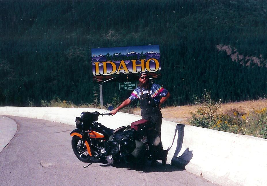1947 Harley Knucklehead motorcycle and rider in tie-dye at Idaho border sign