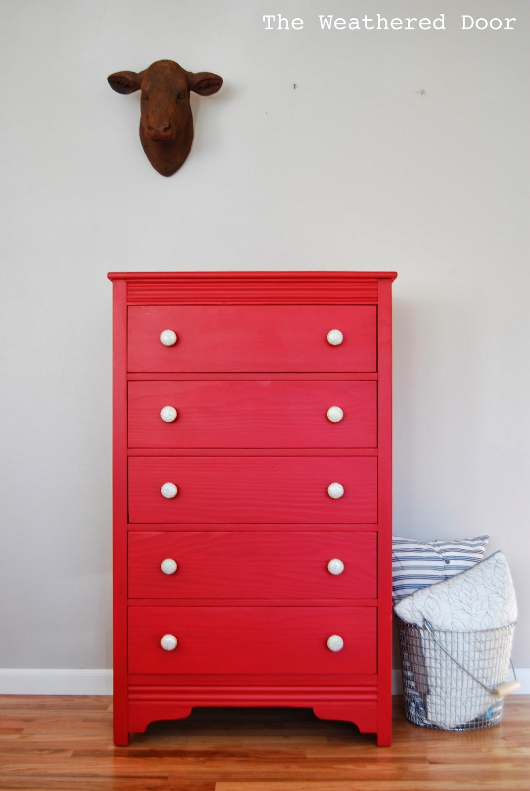 A Tall Red Dresser With Silver And White Knobs The
