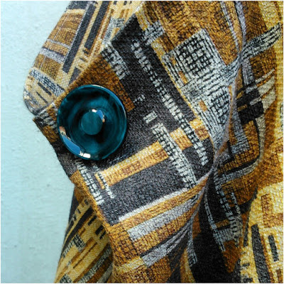 The dress has two huge pockets, each finished with a vintage big teal button.