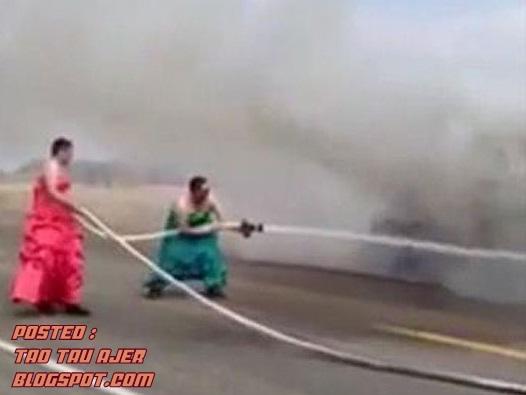 2 orang bomba berpakaian gaun memadamkan kebakaran