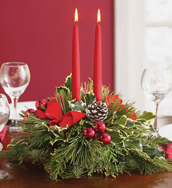 Dos velas junto a pascuas navideñas