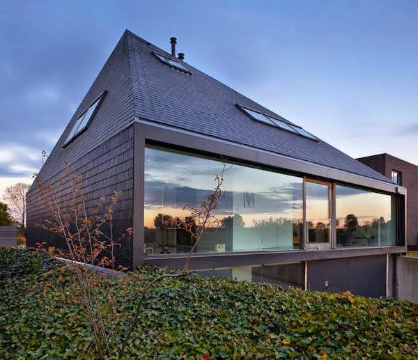 Unusual home stands out among its surroundings as a for High pitched roof house plans