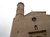 La façana de migdia, totalment llissa amb la portalada entre dues columnes i la rosassa
