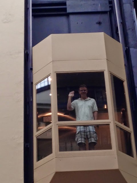 Man in glass elevator going up.
