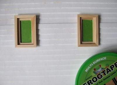 Undercoated wall of a dolls' house miniature kit, with windows covered with Frogtape.