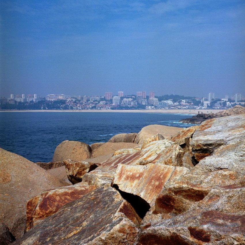Pedras à Beira mar para travarem a força das ondas e paisagem da Cidade do Porto, ao longe