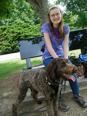 Alfie in harness, standing and panting hard in front of Charissa, who is seated on a park bench.