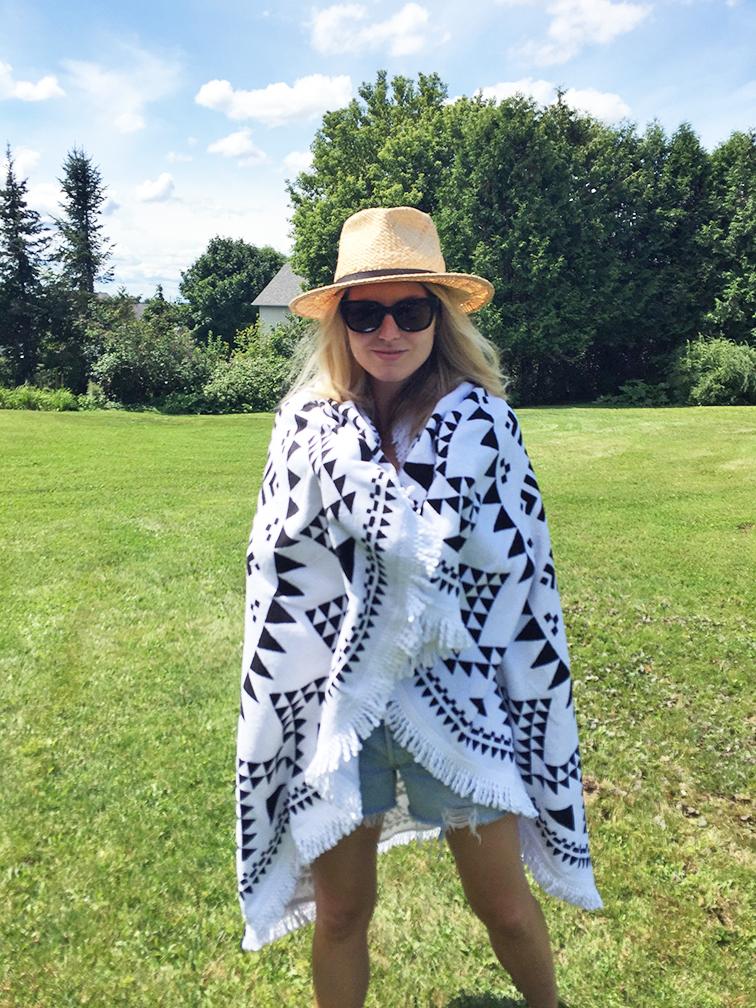 Levi's cutoffs, Raen sunglasses, We Are Summer round Marfa throw, Dorfman Pacific straw hat, black