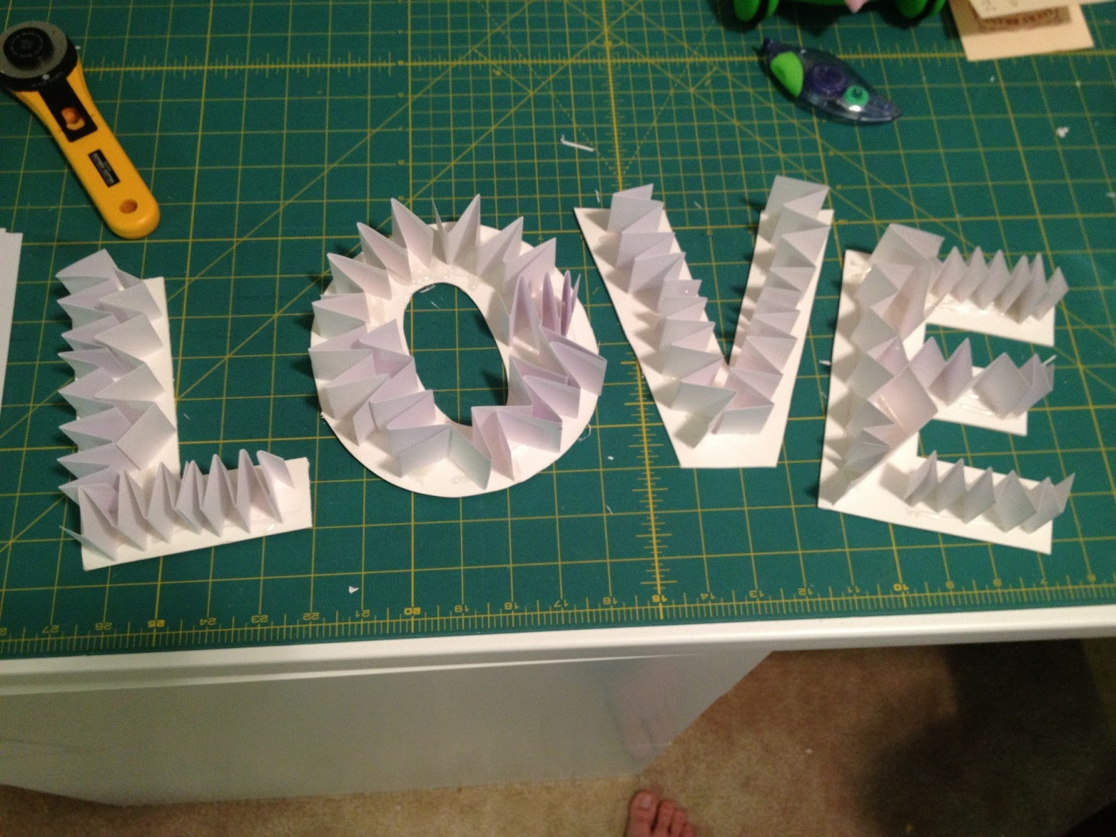 next cut a bunch of 1 inch strips out of card stock and accordion them using the hot glue gun attach them to one side of the letters