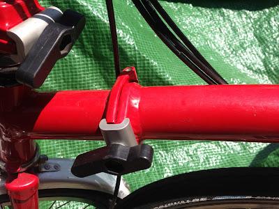 Red Brompton folding bike showing older hand brazed main hinge