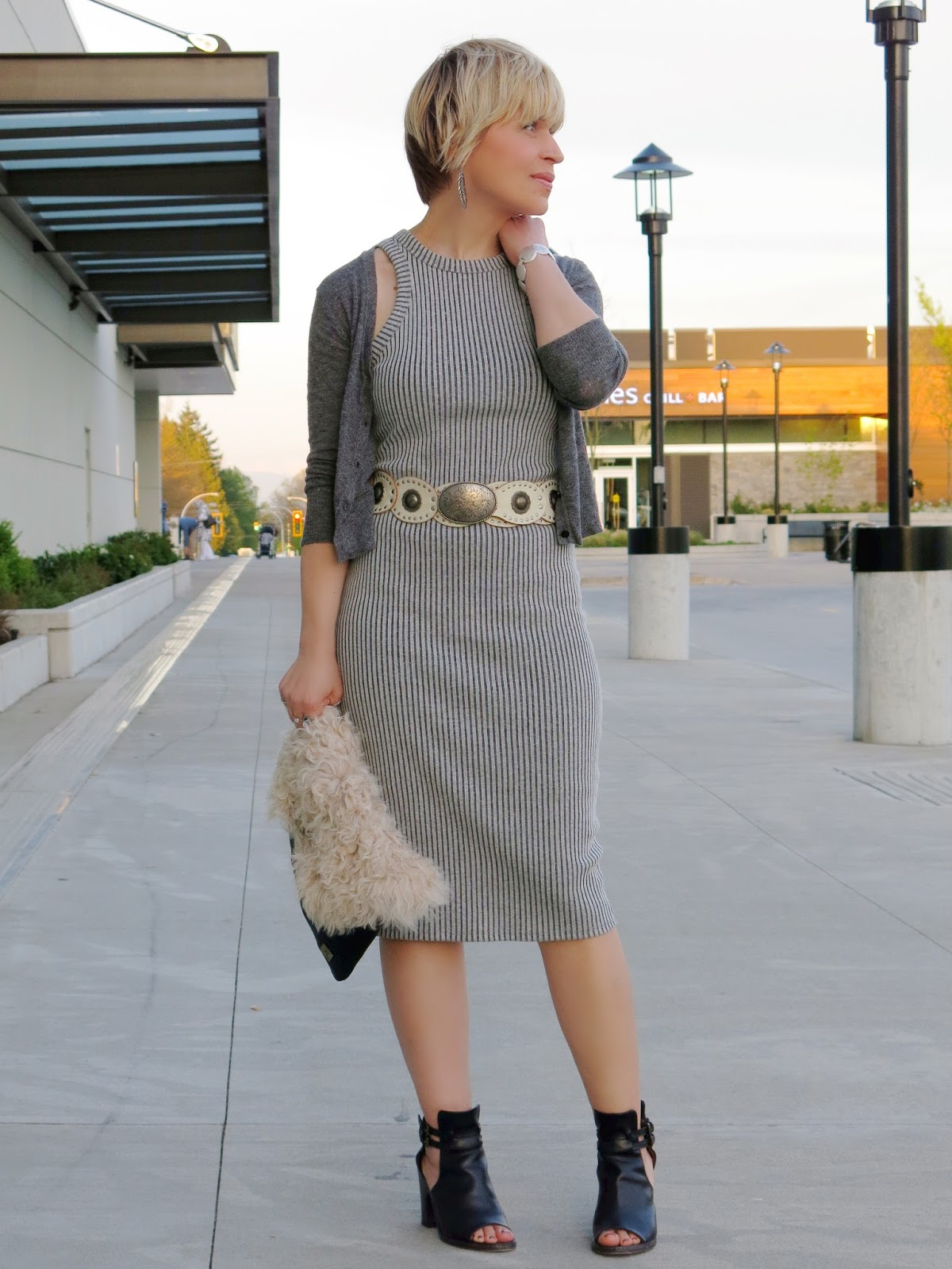 styling a tank dress with a shrunken cardigan, cut-out booties, and a furry clutch