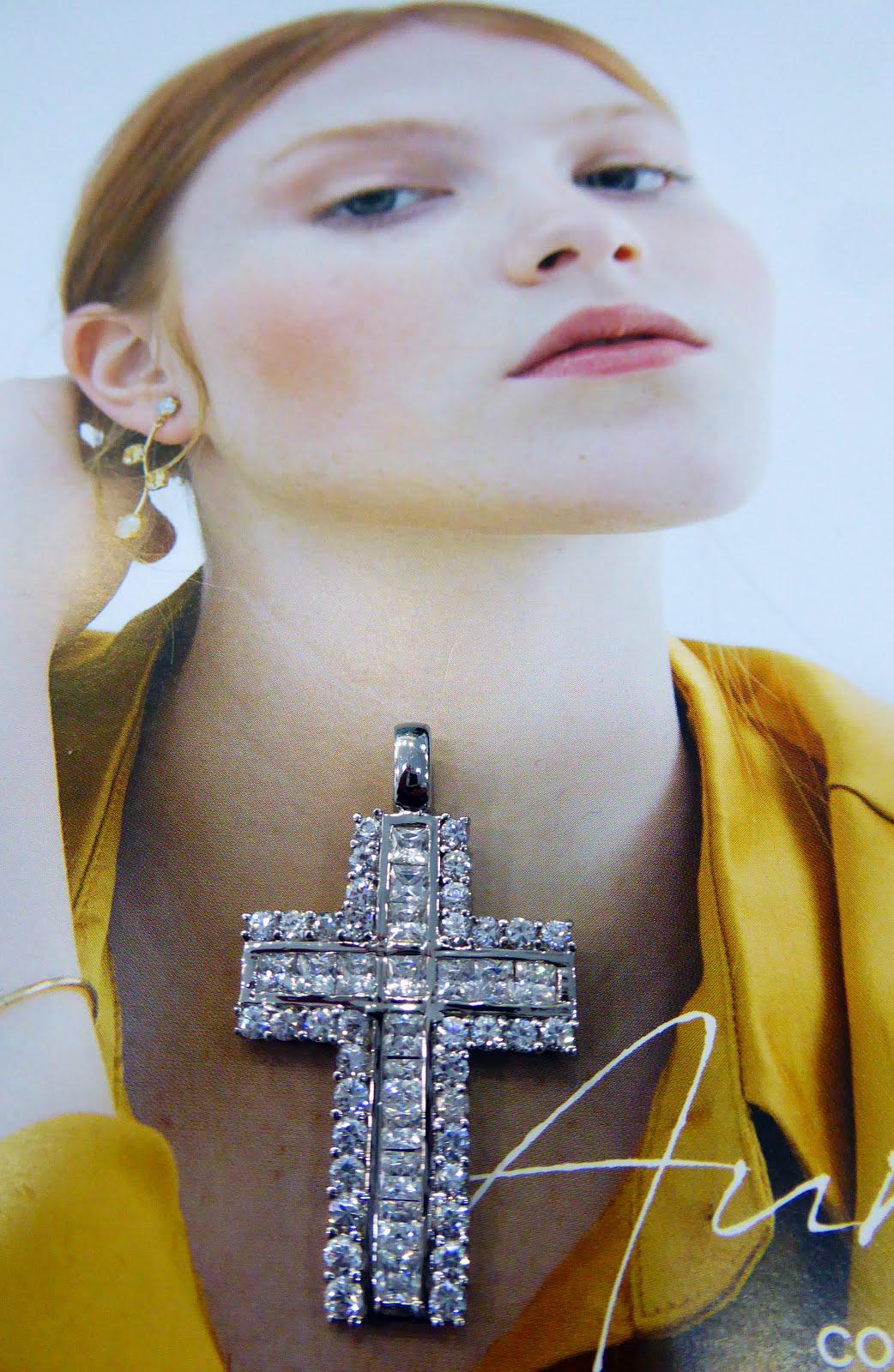 Una cruz de plata llena de circonitas.