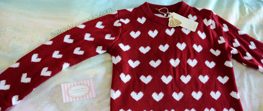 The Sweetbox Store red heart sweater, laid flat.