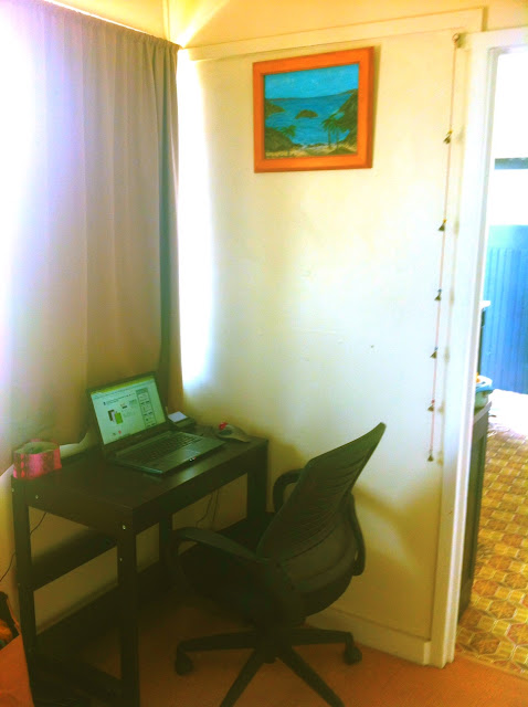 Photo of my small desk underneath a window in the living room. My new laptop is on it and a painting of an ocean scene hangs above.