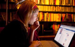 chica revisando su facebook en la laptop