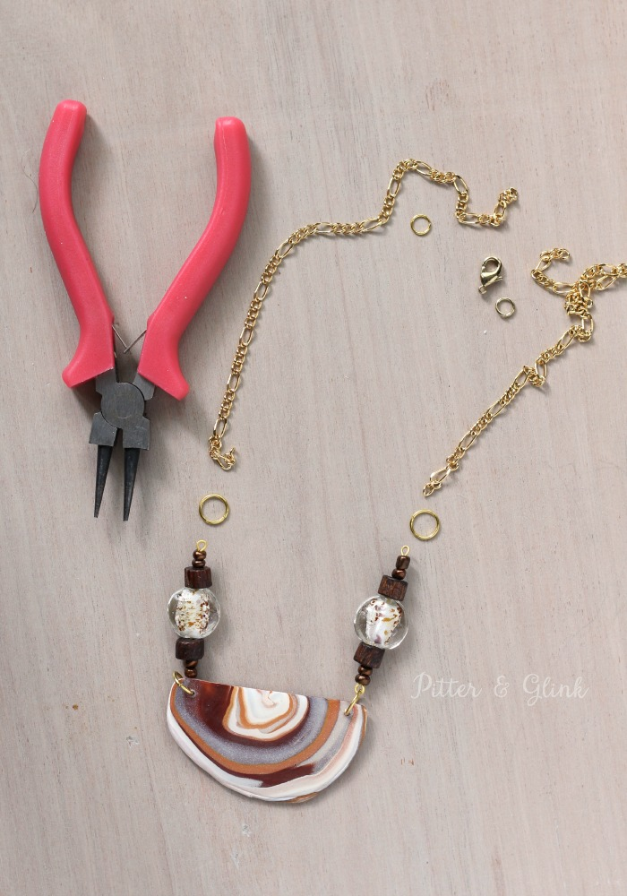 Create a beautiful DIY boho-inspired necklace featuring a faux agate pendant made from polymer clay. www.pitterandglink.com