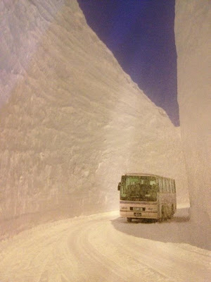 Coach bus driving in snow-packed road between flat-sided snow walls two stories high