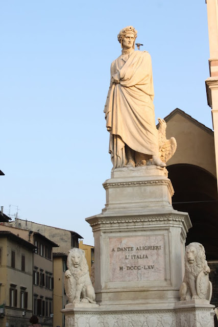 A statue is displayed in front of Basilica of Santa Croce Florence in Florence, Italy