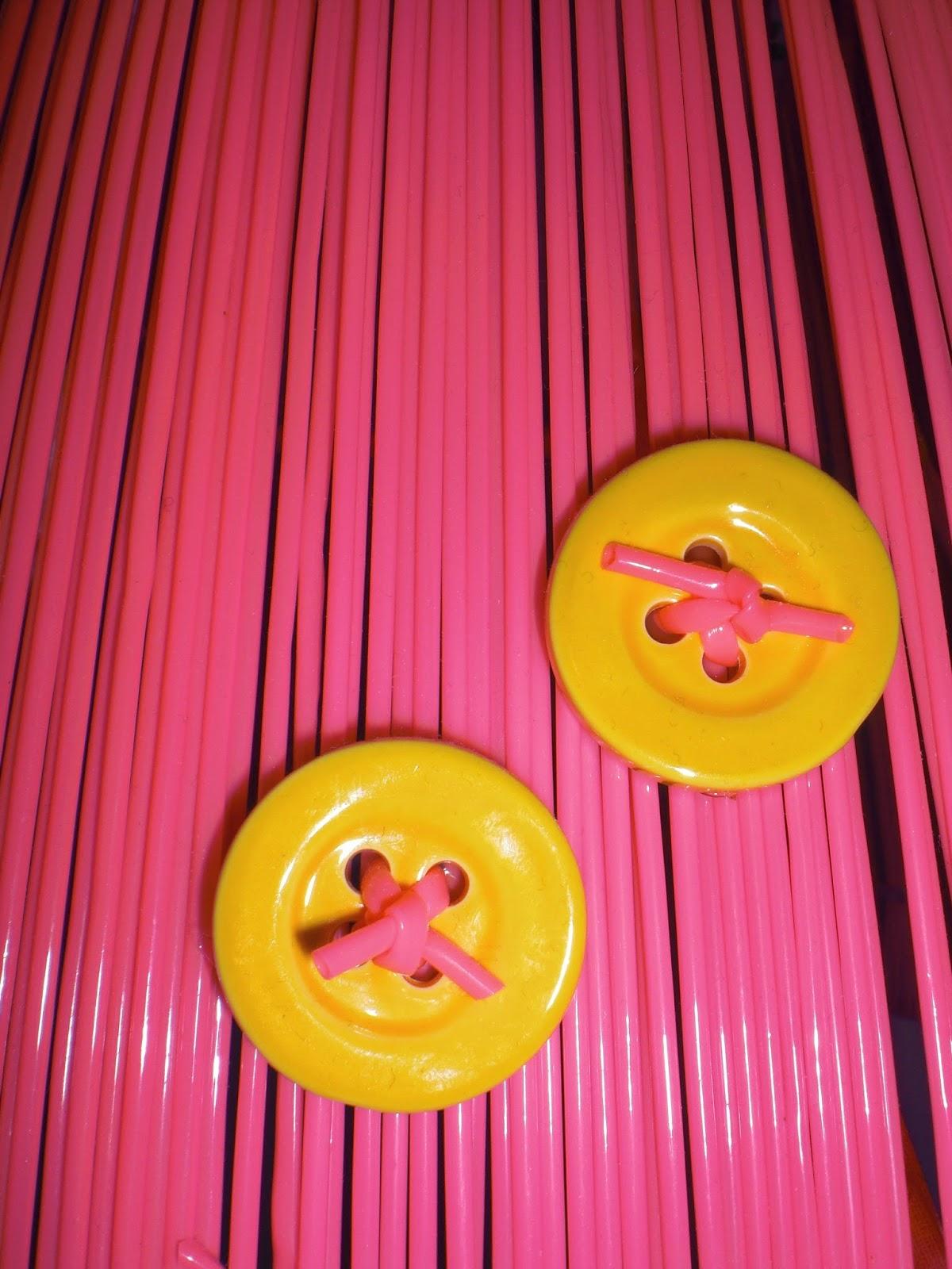 Neonpink lampeskærm med gule knapper.