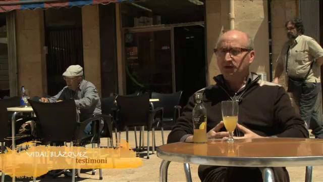 Fotograma del documental on se'm veu passant per darrera d'un entrevistat a una terrassa de la Plaça de la Font