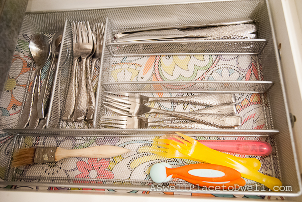 organized utensil drawer, lined in wrapping paper.
