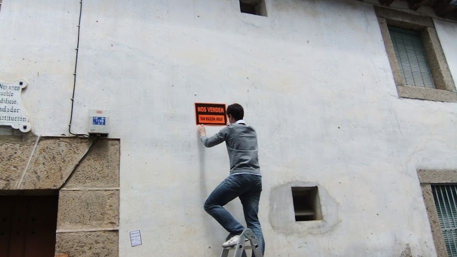 Un miembro de IU coloca un cartel en el exterior del edificio del Asilo en Candelario