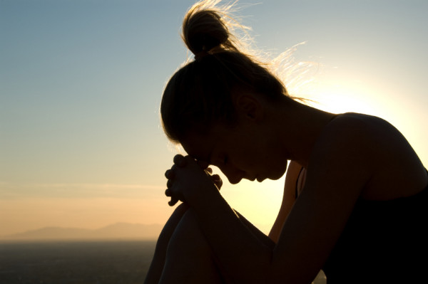 Žena sedi sama, spuštene glave