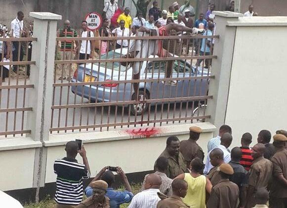 Maofisa wa Polisi na Magereza wakiangalia mwili wa mtu aliyekuwa