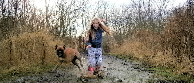 girl and dog running through muddy water wet puddle splash