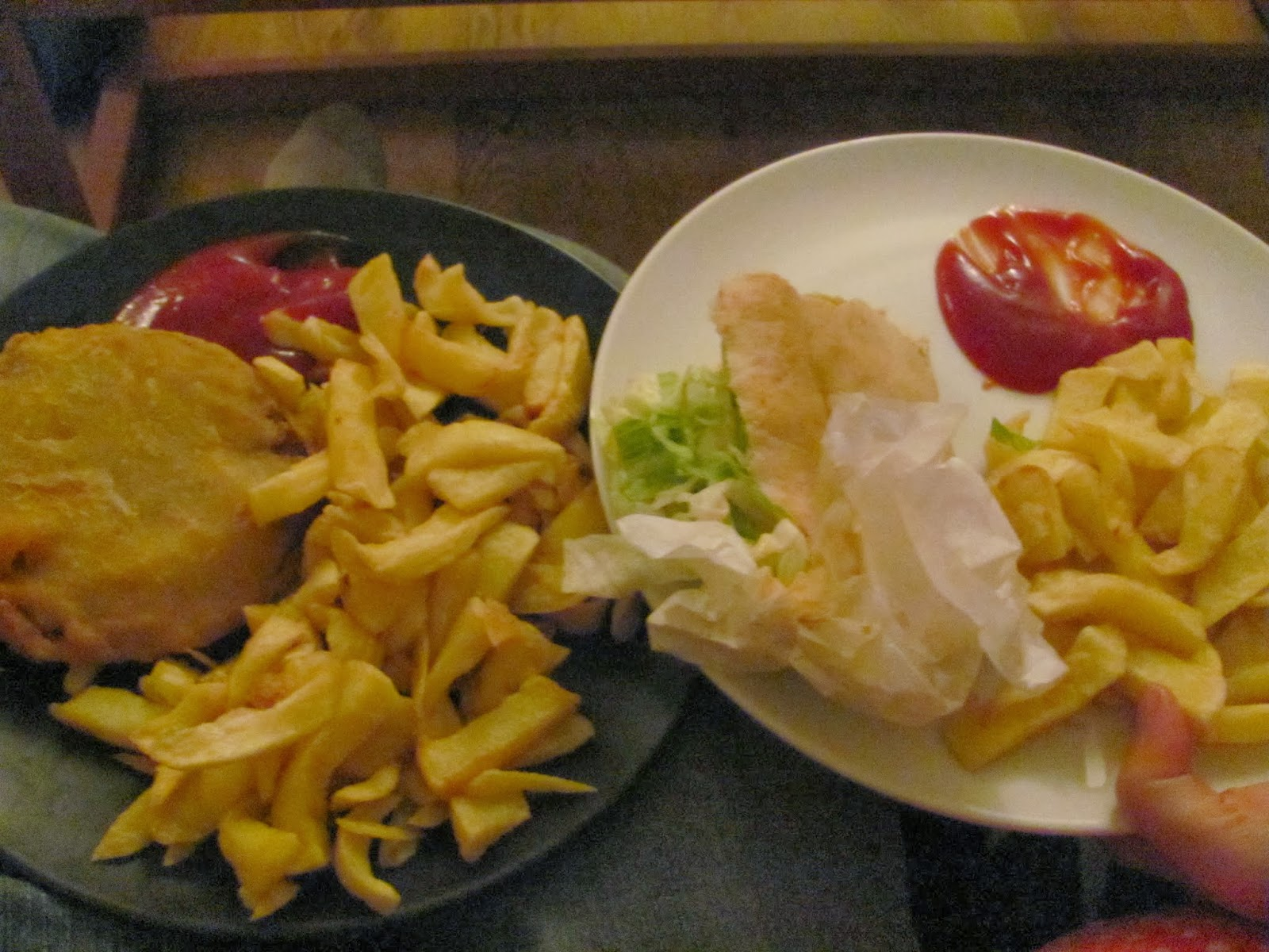 A battered, fried hamburger and a veggie falafel with chips