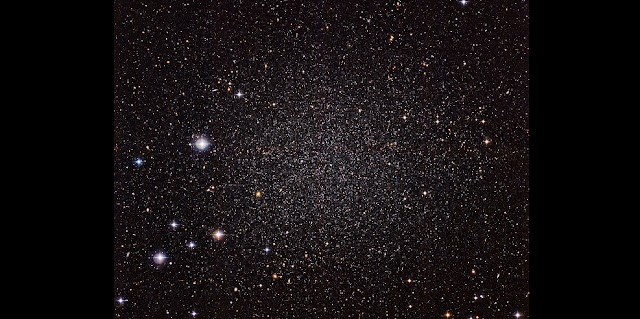 The Sculptor Dwarf Galaxy, pictured in a new image from the Wide Field Imager camera, installed on the 2.2-metre MPG/ESO telescope at ESO's La Silla Observatory, is a close neighbour of our galaxy, the Milky Way. Despite their proximity, both galaxies have very distinct histories and characters. This galaxy is much smaller, fainter and older than the Milky Way and appears here as a cloud of faint stars filling most of the picture.  Many other much more distant galaxies can be seen shining right through the sparse stars of the Sculptor Dwarf. Credit: ESO