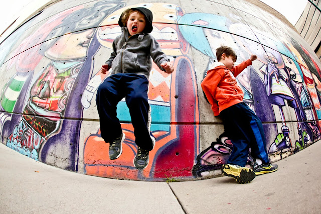 Two little boys jumping and dancing in front of a David Choe mural in Denver, Colorado.