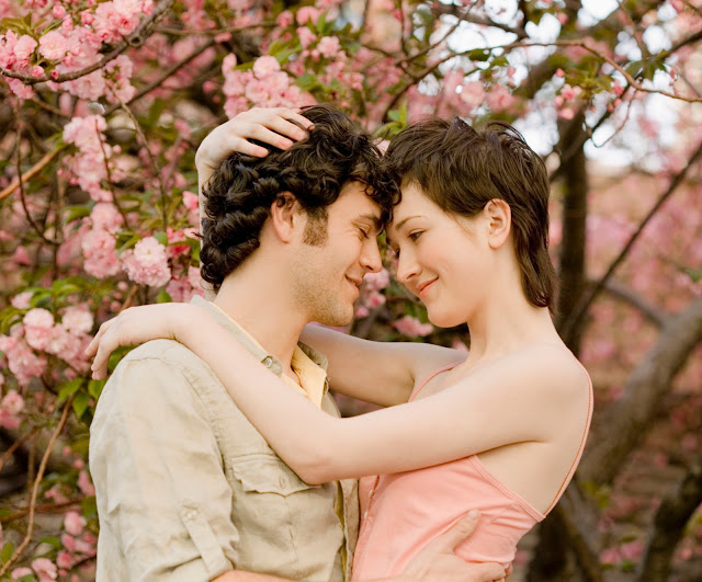 Young couple intimately embracing standing in front of flowers blooming on a tree.