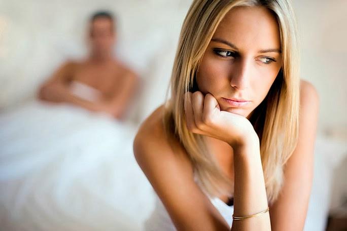 Mujer preocupada sentada en la cama que comparte con su compañero.