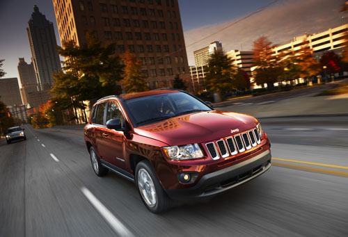 Front three-quarters view of red2012 Jeep Compass Latitude driving on city street