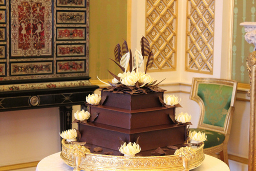 The flawless square cake rose up three tiers above its golden stand at the