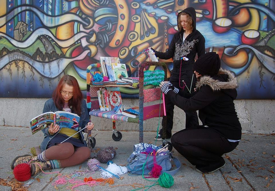 Three women knit colorful swatches and attach the swatches to a wheeled book cart. Books about knitting are shelved on the cart. In the background, an exterior building wall is covered with a colorful mural.