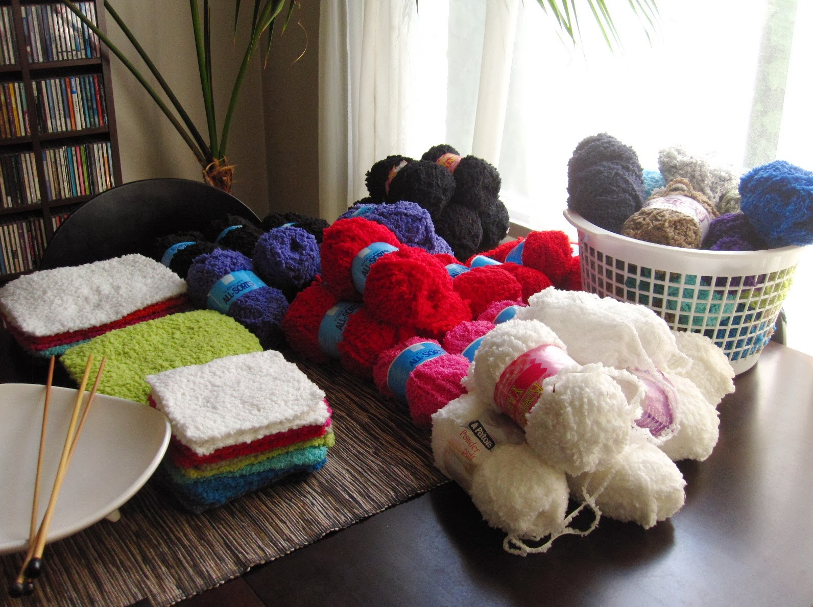 Dining table covered in balls of fluffy yarn and completed dolls house flokati rugs