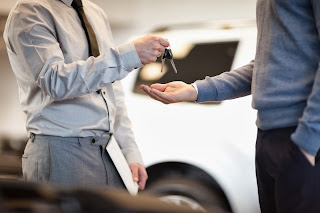 salesman giving customer car keys