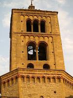 Detall del campanar de tres pisos amb finestres senzilles, biforades i triforades