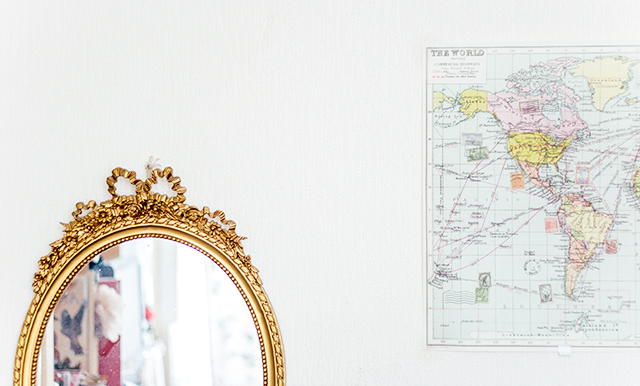 gold framed mirror and world map