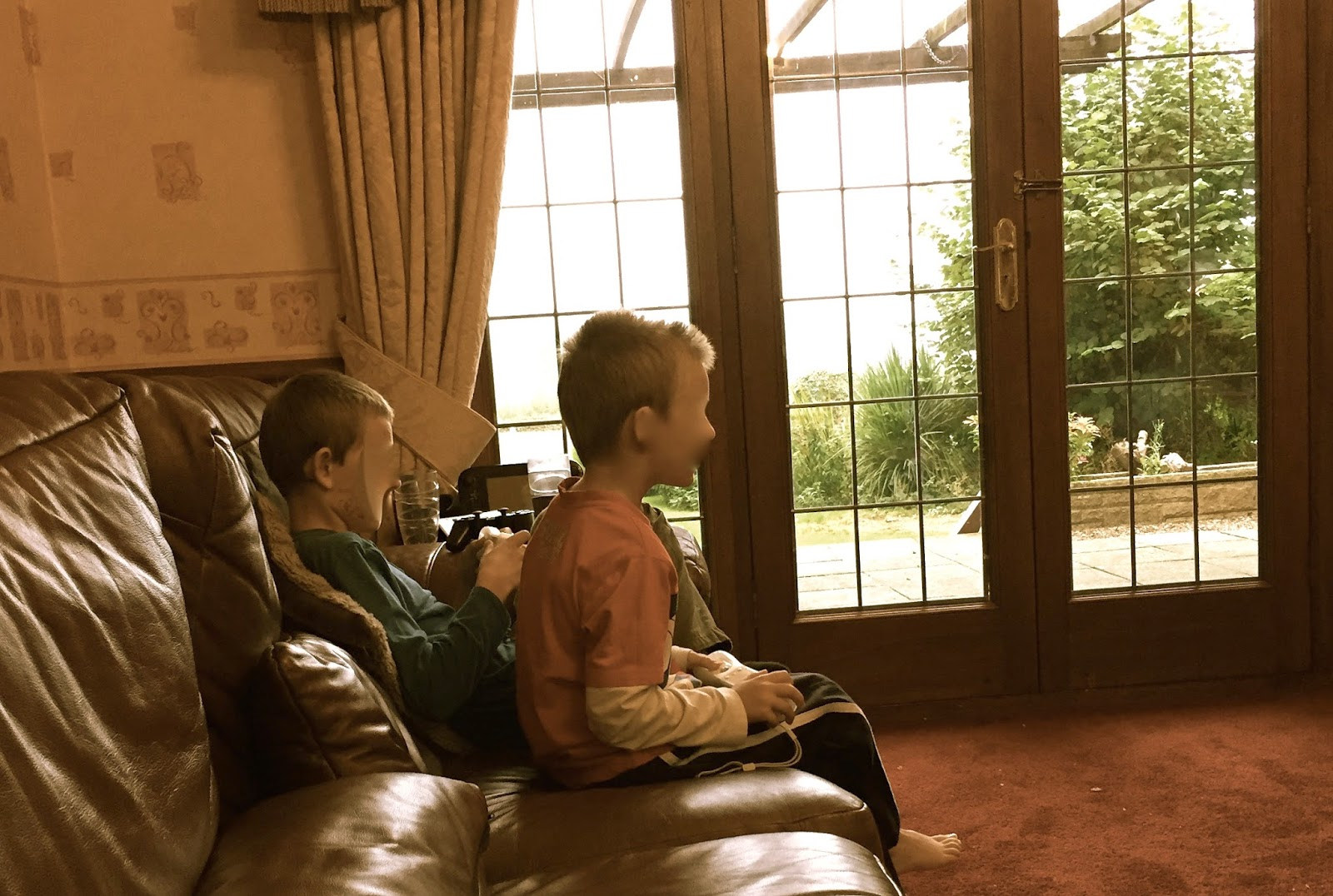 Morgan's Milieu | Forget About Technology: Two boys sat on a brown leather sofa playing games.