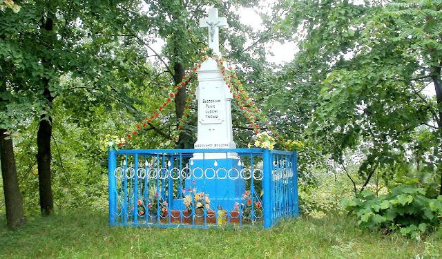 Krzyż przy wjeździe do wsi z 1922 roku. Ustawiony naprzeciw byłego dworu przy wjeździe do wsi od strony Gowarczowa. Foto. Paweł Kałwiński.