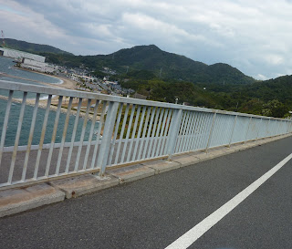 View over the side of the Hakata Oshima bridge with mountains of Oshima and a beach visible. On the Shimanami Kaido Bikeway