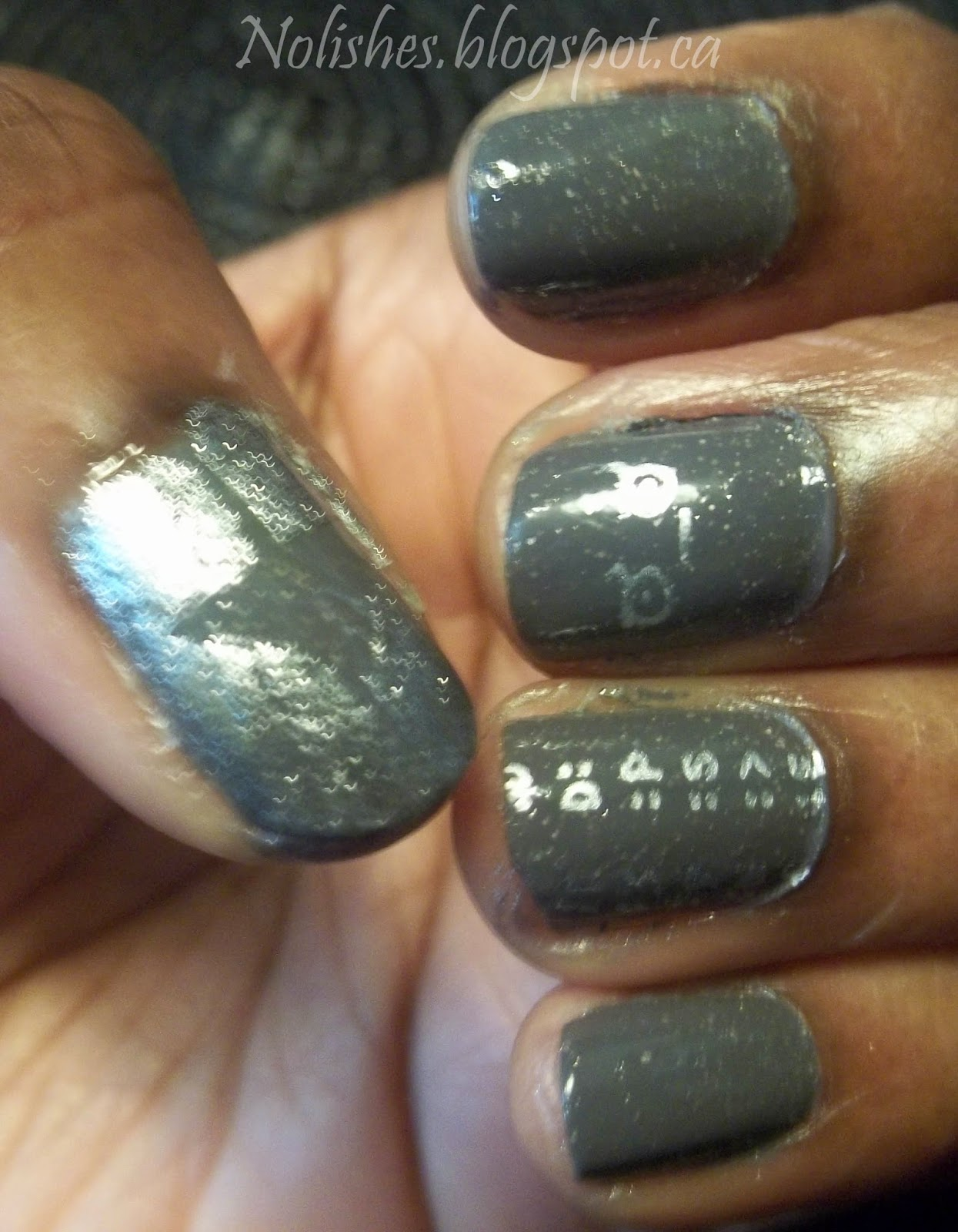 Nail stamping manicure featuring grey nail polish with silver microglitters stamped with silver emoticon images on ring and middle fingers. The thumbnail has silver shatter polish over the grey base colour, but a triangle of grey base polish with no shatter topcoat, remains in the centre of the nail.