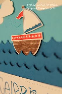 Close-up view of the stamped and cut-out ship sailing in the card stock waves.